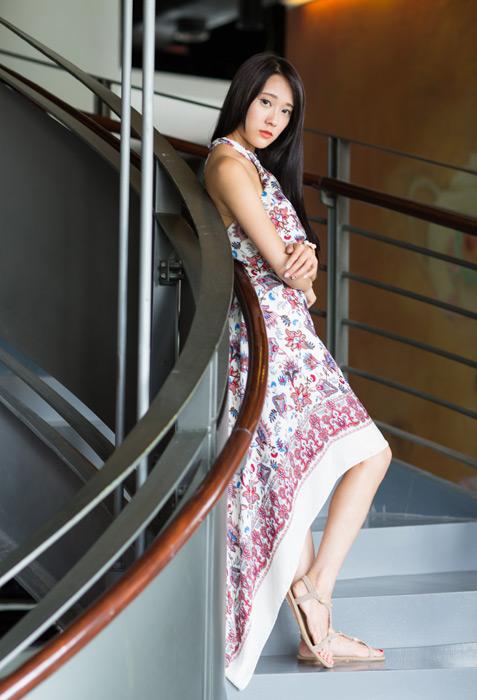 フリー写真 腕を抱えながら階段に立つ女性のポートレイト