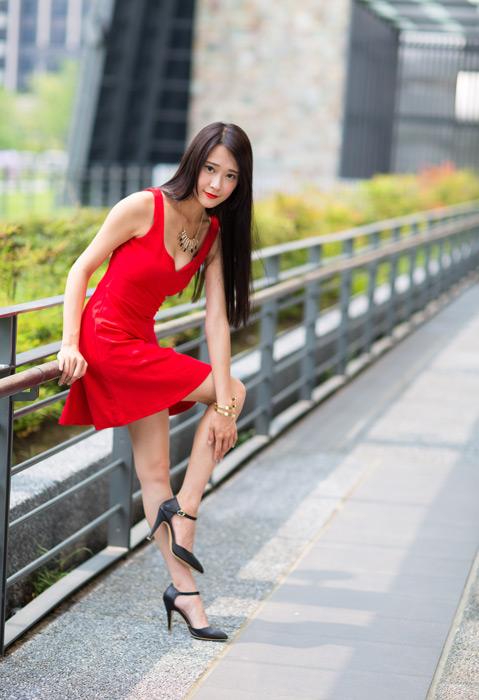 フリー写真 赤いドレス姿で足に手を当てる女性