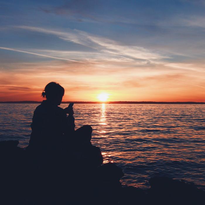 フリー写真 夕日とスマホを操作する女性