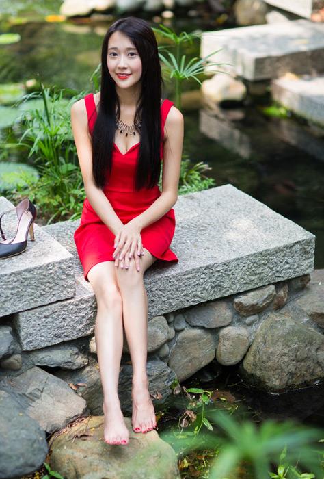 フリー写真 赤いドレス姿で石の上に座る女性のポートレイト