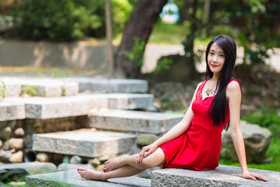 フリー写真 赤いドレス姿で横座りする女性のポートレイト