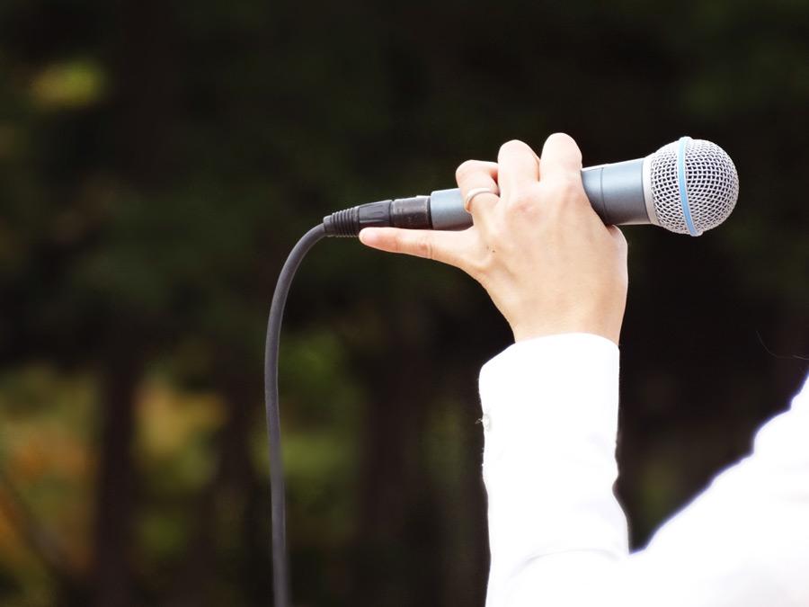 フリー写真 マイクを持って歌うミュージシャンの手
