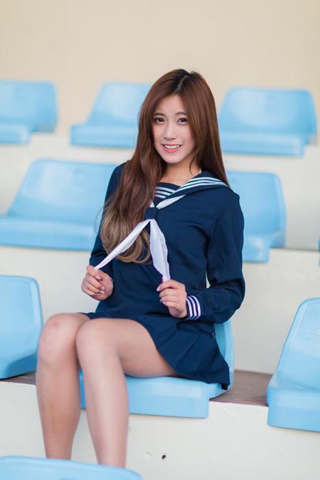 フリー写真 野球のスタンドに座ってセーラー服のスカーフを持つ女子高生