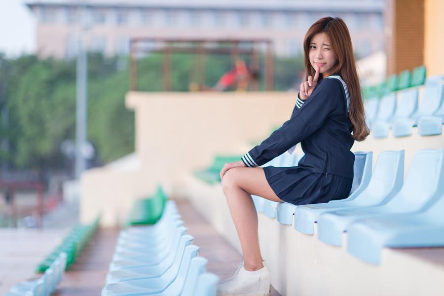 フリー写真 野球のスタンドに座ってウインクする女子高生
