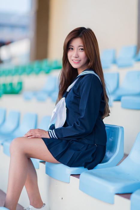 フリー写真 セーラー服姿で野球のスタンドに座る女子学生
