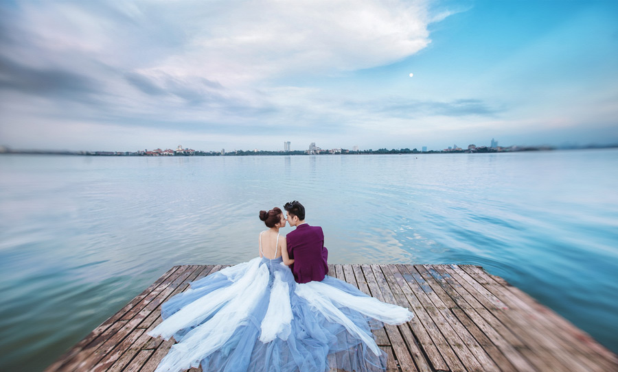 フリー写真 桟橋に座る新郎と新婦