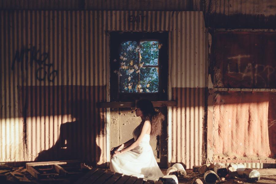 フリー写真 廃墟の中で横を向いてしゃがむ外国人女性