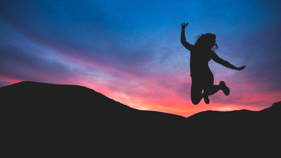 フリー写真 夕焼けとジャンプする少女のシルエット