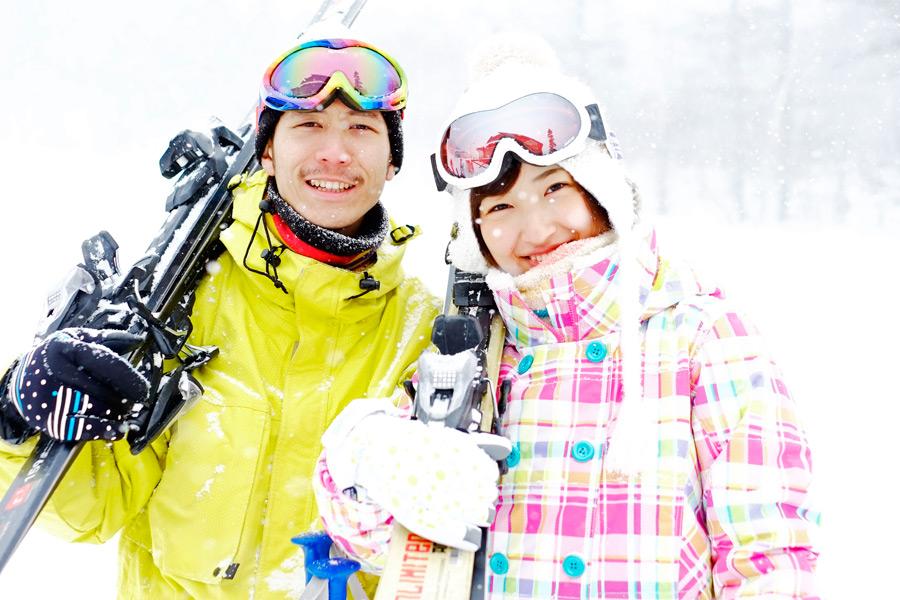 フリー写真 スキー場でスキー板を担ぐカップル