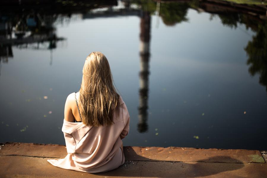 フリー写真 池の前に座っている外国人女性の後ろ姿