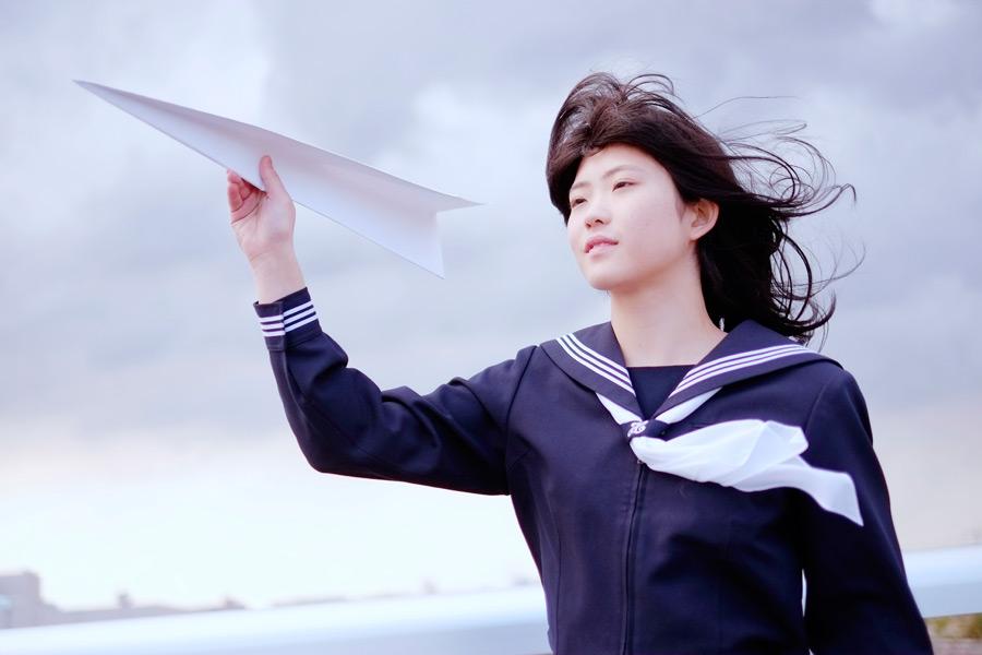 フリー写真 セーラー服姿で紙ひこうきを飛ばそうとする女子高生