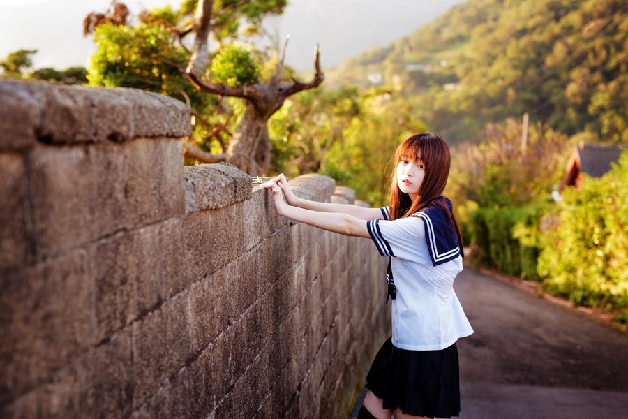 フリー写真 セーラー服姿でブロック塀に手をつく女子高生
