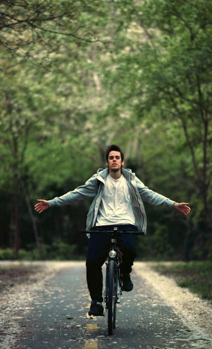フリー写真 自転車で手放し運転で並木道を通る外国人男性