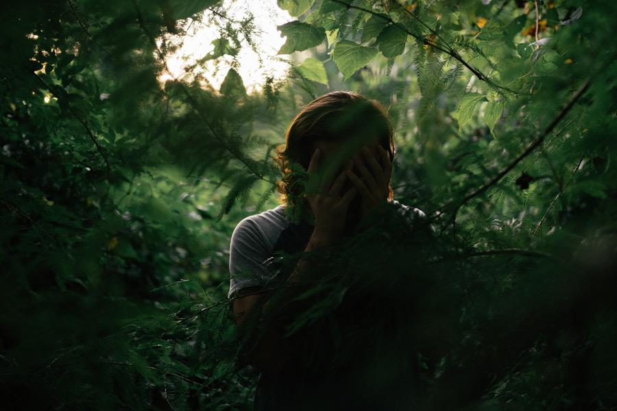 フリー写真 枝葉と手で顔を覆う人物