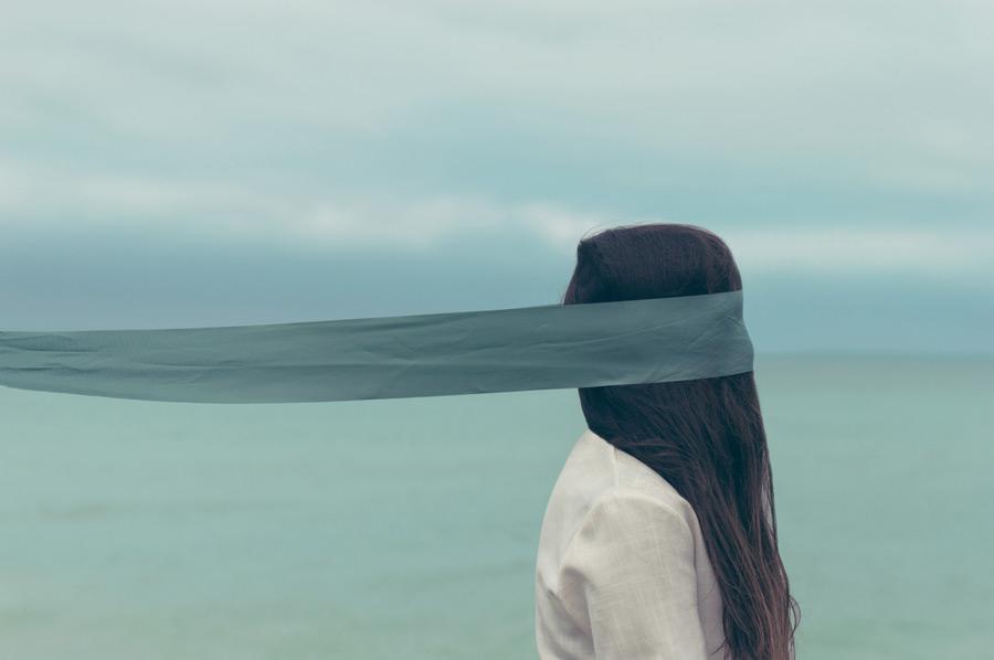 フリー写真 背景の海と目隠しをした女性