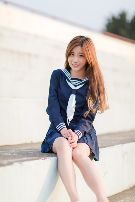 フリー写真 セーラー服姿で観客席に座る女子高生のポートレイト