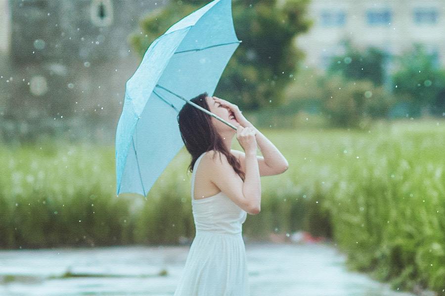 フリー写真 雨の中顔に手を当てて笑う女性のポートレイト