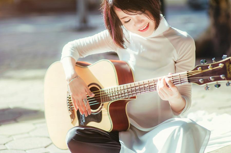 フリー写真 アオザイ姿でギターを弾くベトナム人女性
