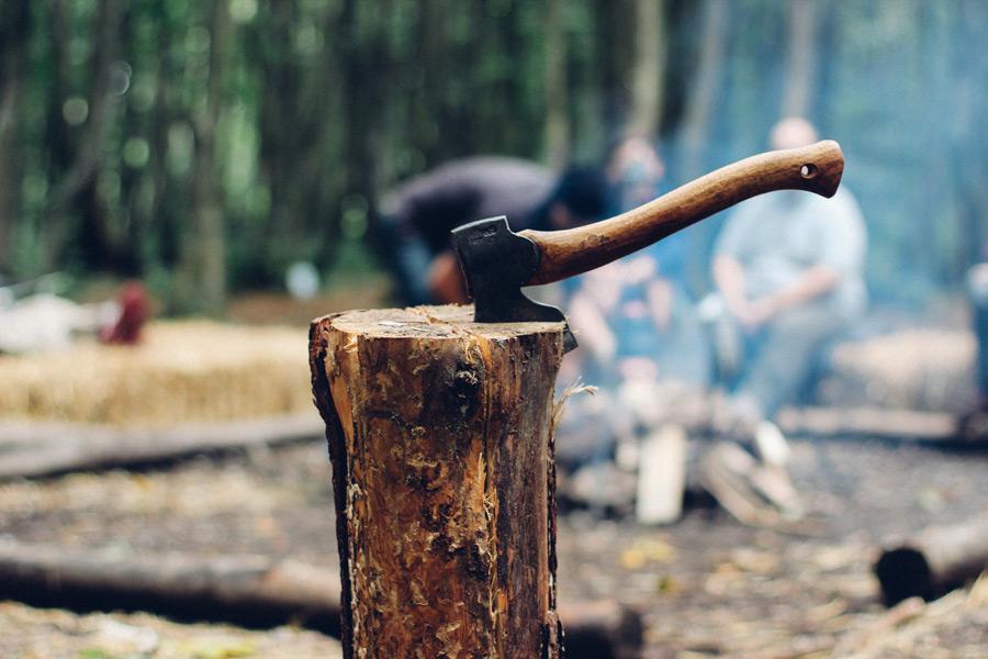フリー写真 薪を割った手斧とキャンプをする人々