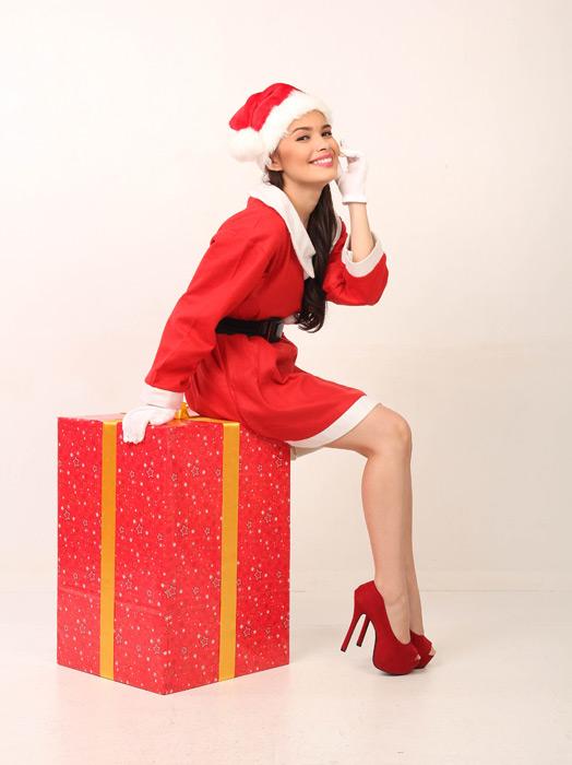 フリー写真 サンタの衣装でプレゼントの上に座る女性