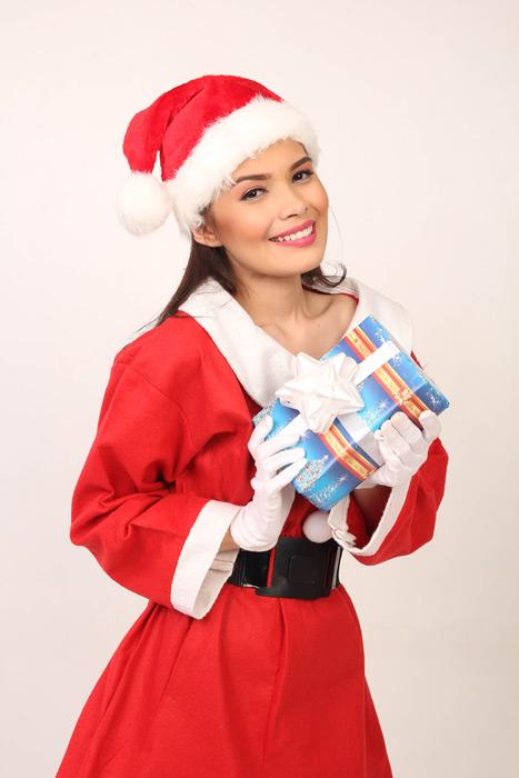 フリー写真 サンタの衣装でクリスマスプレゼントを持つ女性