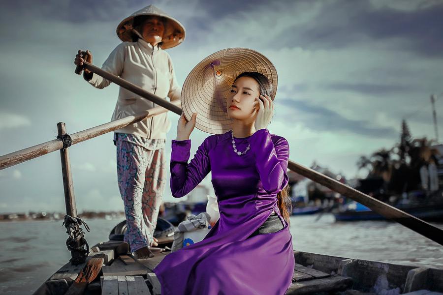 フリー写真 ノンラーとアオザイ姿で渡し船に乗る女性