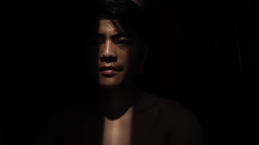 フリー写真 暗闇の中で一筋の光に照らされる男性