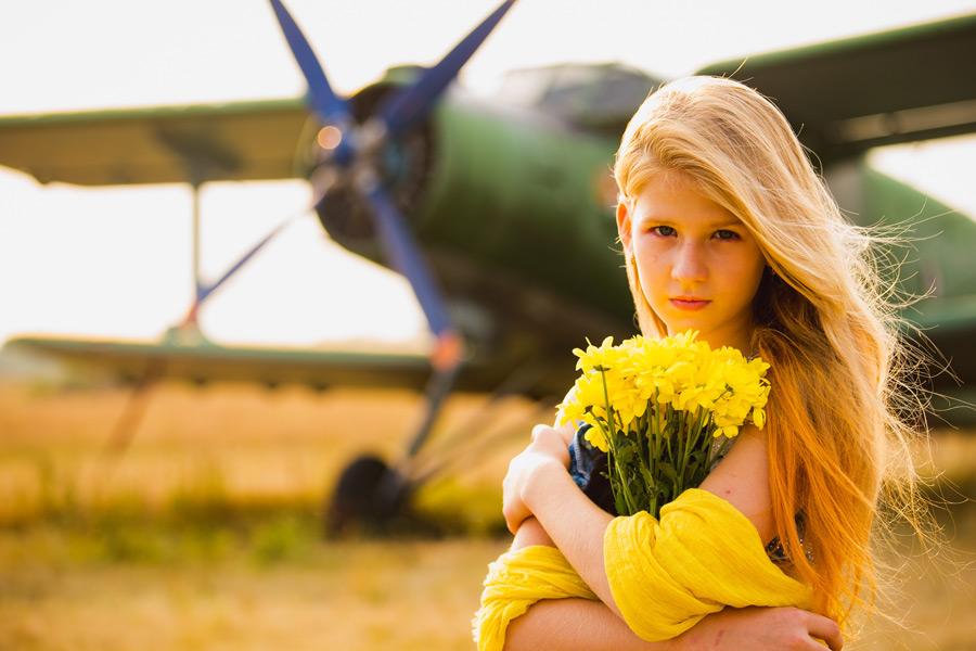 フリー写真 飛行機の前で花束を抱える外国の少女