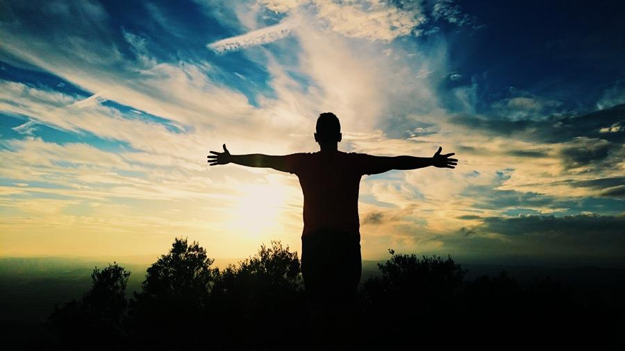フリー写真 夕空と手を広げる男性のシルエット