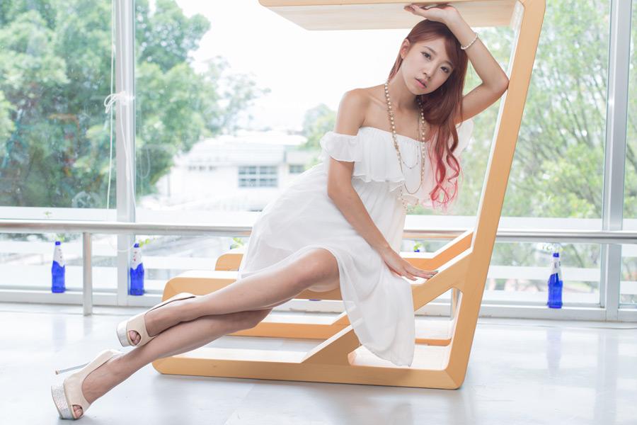 フリー写真 チューブトップのワンピース姿で横座りする女性