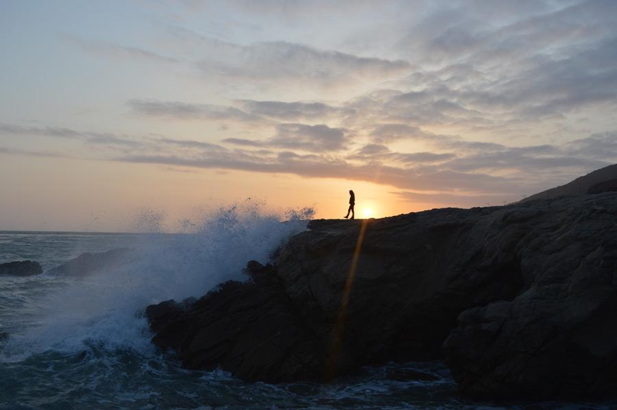 フリー写真 夕日と崖に打ちつける波と人物のシルエット