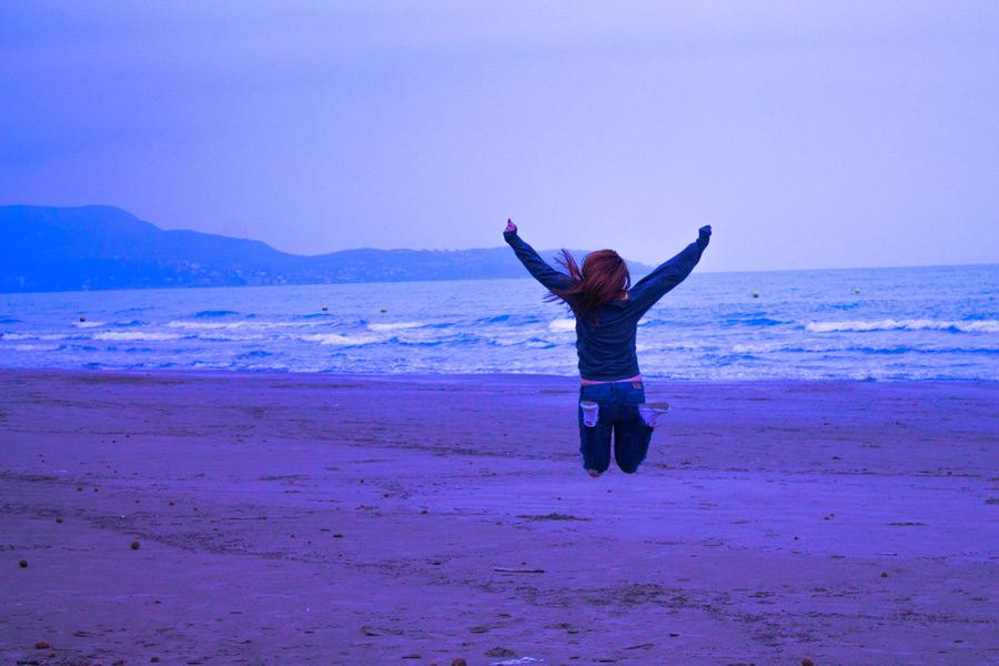 フリー写真 砂浜でジャンプする女性の後ろ姿
