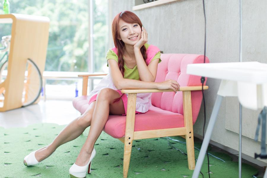 フリー写真 頬杖をつきながらソファーに座る女性のポートレイト