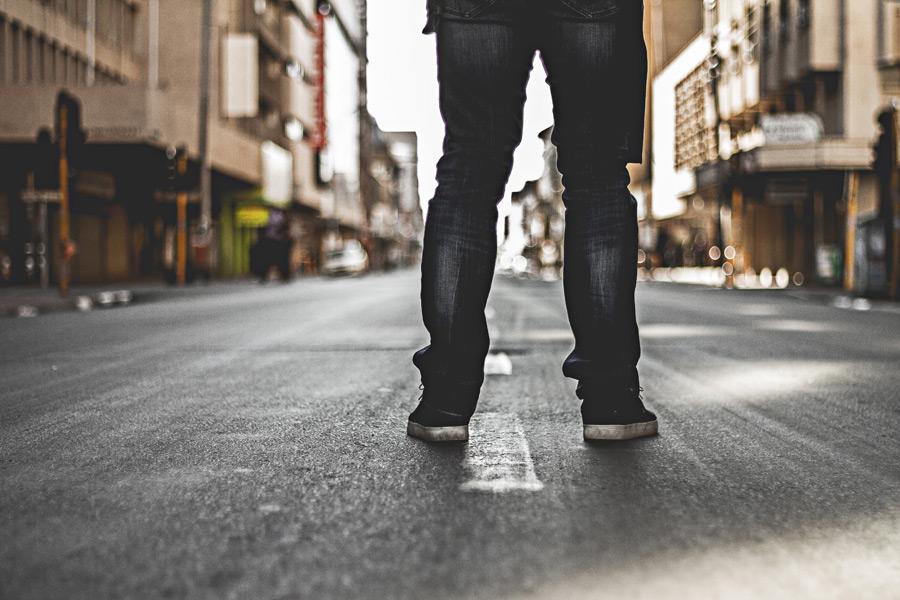 フリー写真 道路の真ん中に立つ後ろ姿の脚