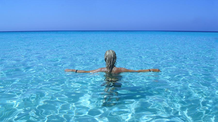 フリー写真 スピアッジャ・デイ・コニッリの海と手を広げる女性の後ろ姿