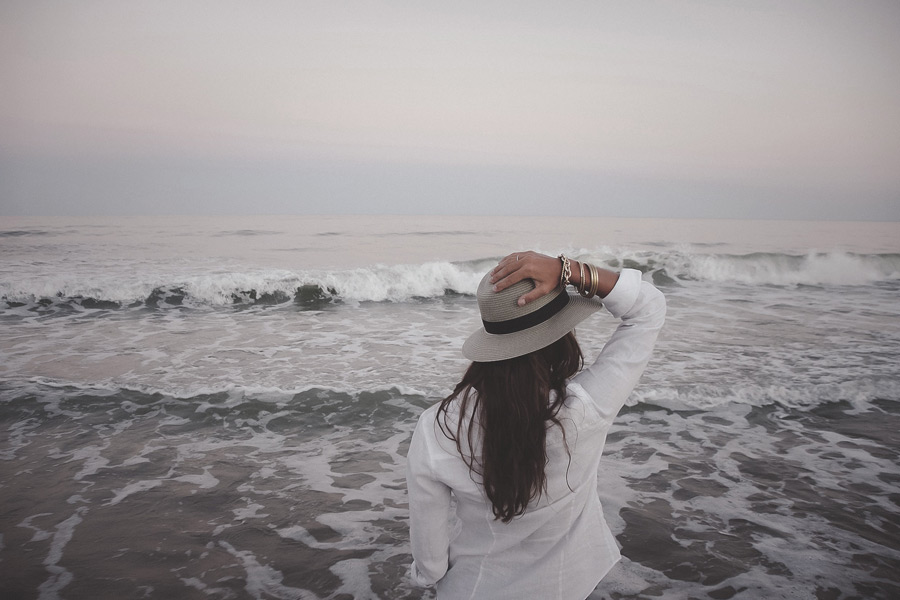 フリー写真 帽子を押さえながら海を眺める女性の後ろ姿