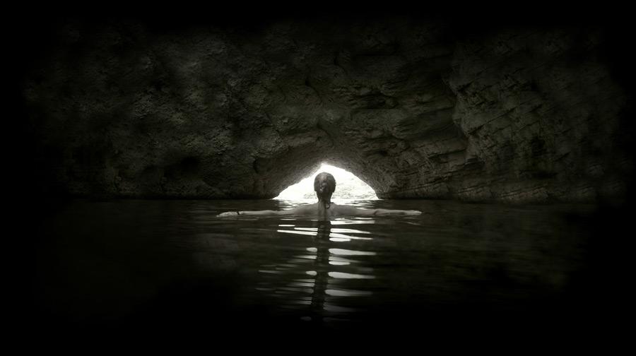 フリー写真 海蝕洞と海に浮かぶ女性