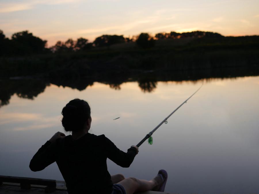 フリー写真 夕暮れの湖で釣りをしている女性
