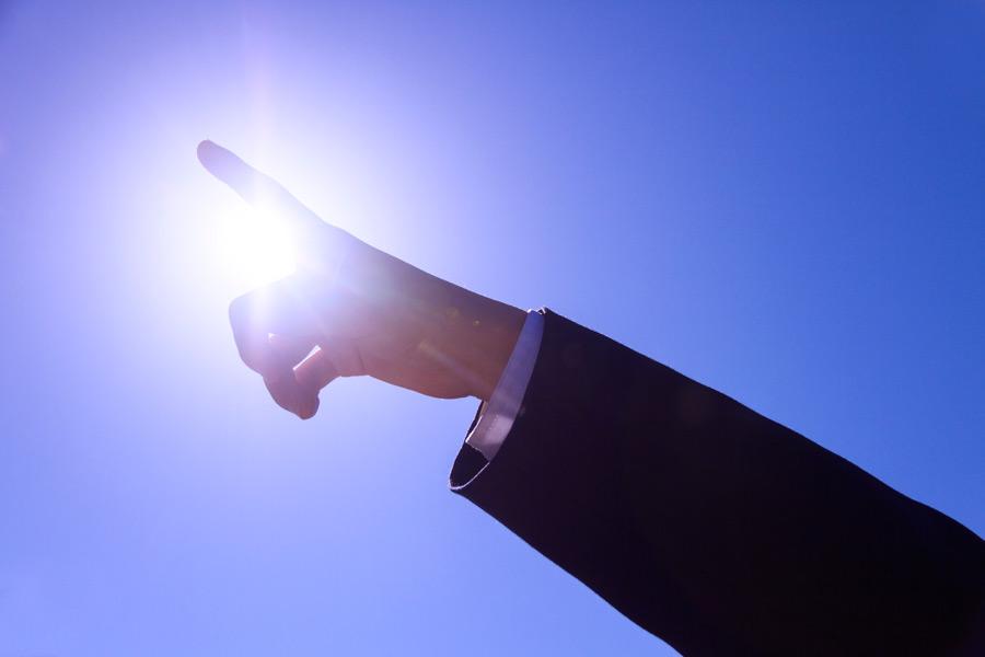 フリー写真 太陽の光と目標に向かって指差すサラリーマンの手