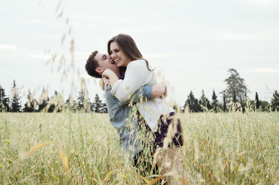 フリー写真 草むらで彼女を抱き上げる彼氏