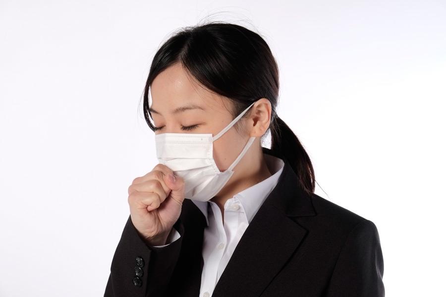 フリー写真 マスクをつけて咳をしている女性社員