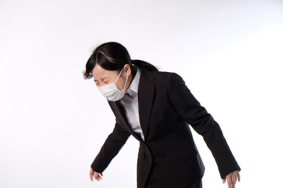 フリー写真 マスクをしてくしゃみをする女性社員