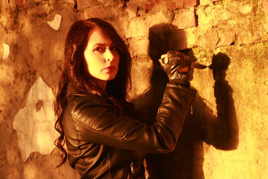 フリー写真 サバイバルナイフを壁に突きつける外国人女性