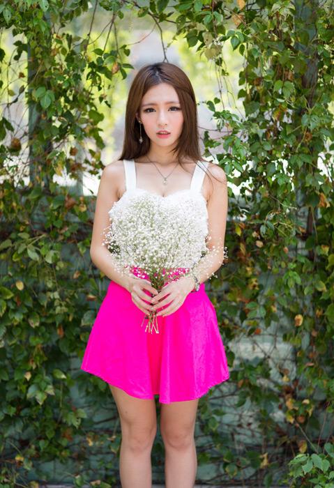 フリー写真 つる植物の壁の前でかすみ草の花束を持つ女性