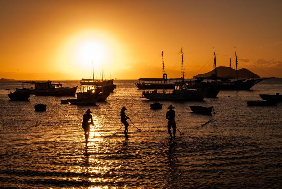 フリー写真 夕暮れの海でボートを引き上げる漁師