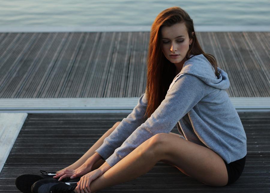 フリー写真 パーカー姿で桟橋の上に座る外国人女性