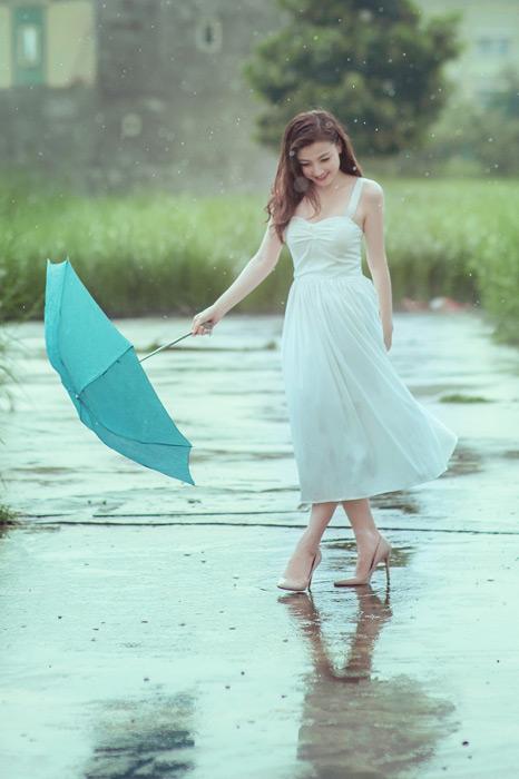 フリー写真 白いドレス姿で雨の中に立つ女性