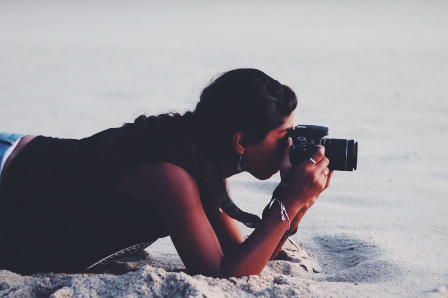 フリー写真 腹這いになってカメラで写真を撮る外国人女性