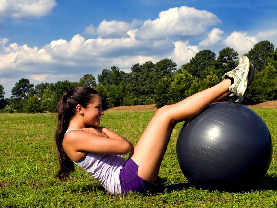 フリー写真 バランスボールを使って腹筋する女性
