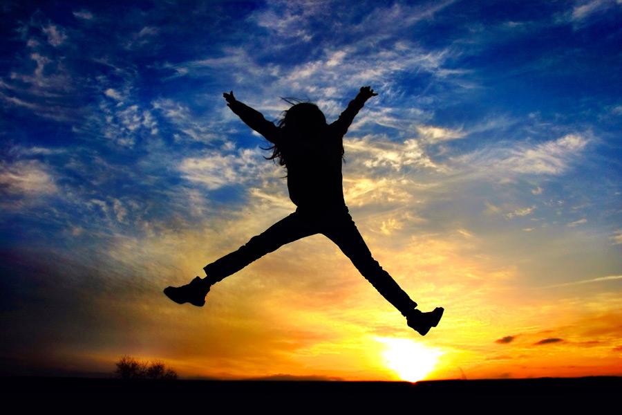 フリー写真 大の字にジャンプする子供と夕日